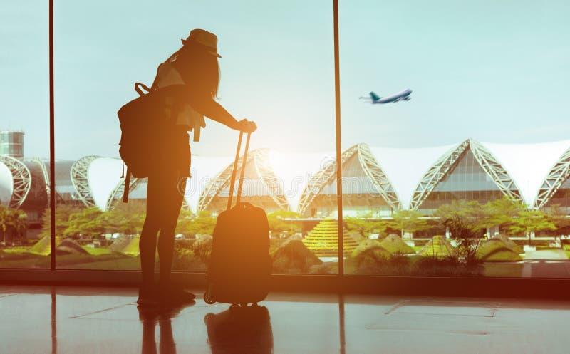 Viajero de la mujer con el aeroplano que espera del equipaje en el aeropuerto fotos de archivo