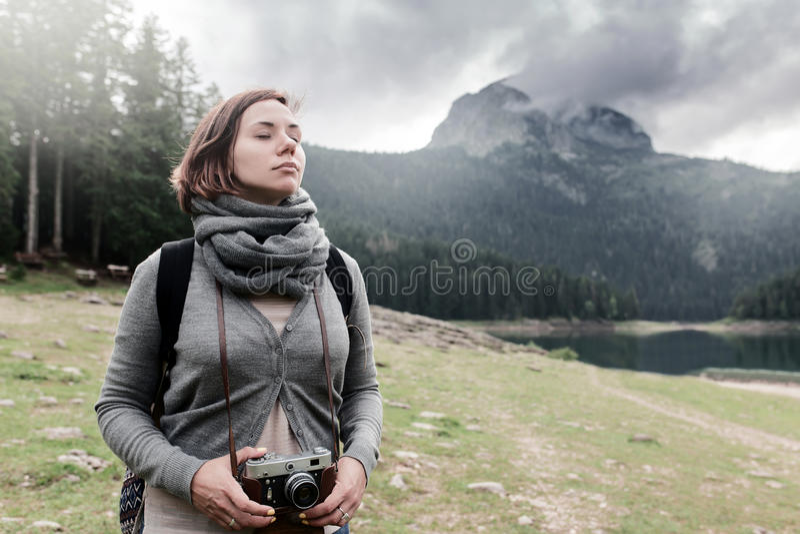 Viajero de la mujer con la cámara del vintage en el paisaje hermoso de la naturaleza fotografía de archivo libre de regalías