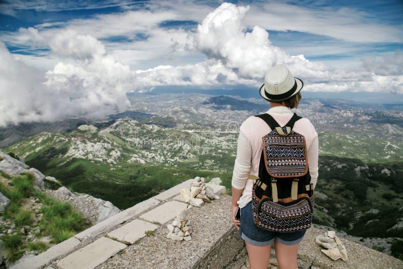 Viajero de la mujer con la mochila que se coloca en la alta montaña imagen de archivo libre de regalías