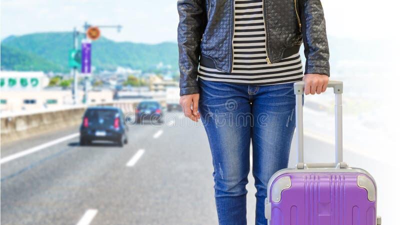 viajero de la mujer con la maleta aislada en la carretera japonesa con m imagen de archivo