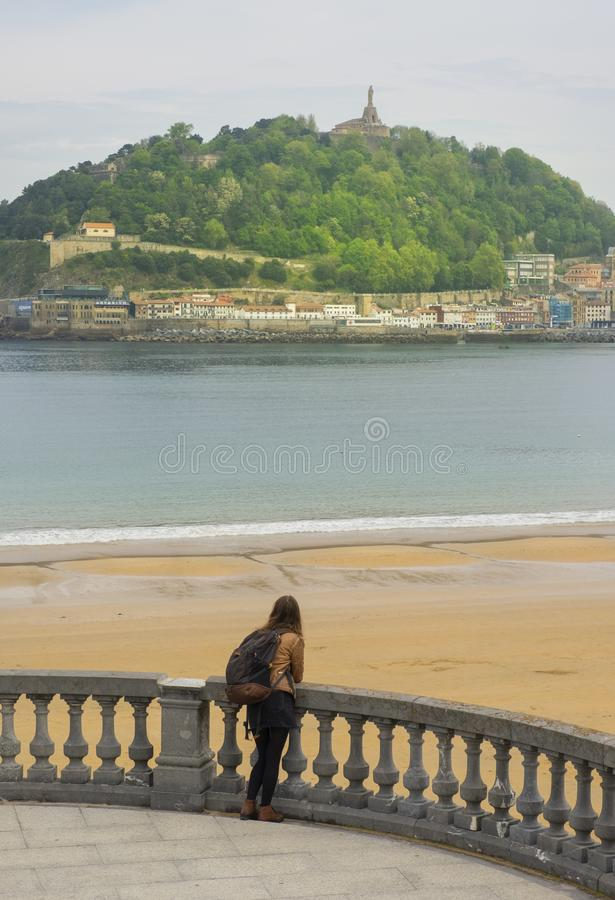 Viajero de la mujer joven con caminar de la mochila al aire libre cerca del mar en la ciudad de San Sebastian fotos de archivo