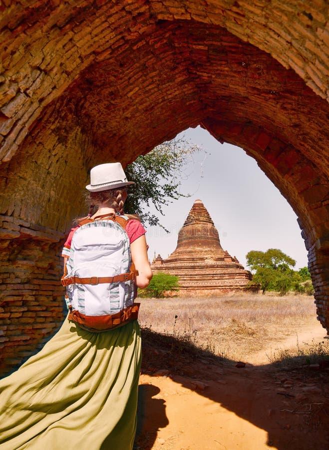 Viajero de la mujer joven con una mochila que camina con el Bagan viejo que mira los stupas budistas antiguos birmania fotos de archivo libres de regalías
