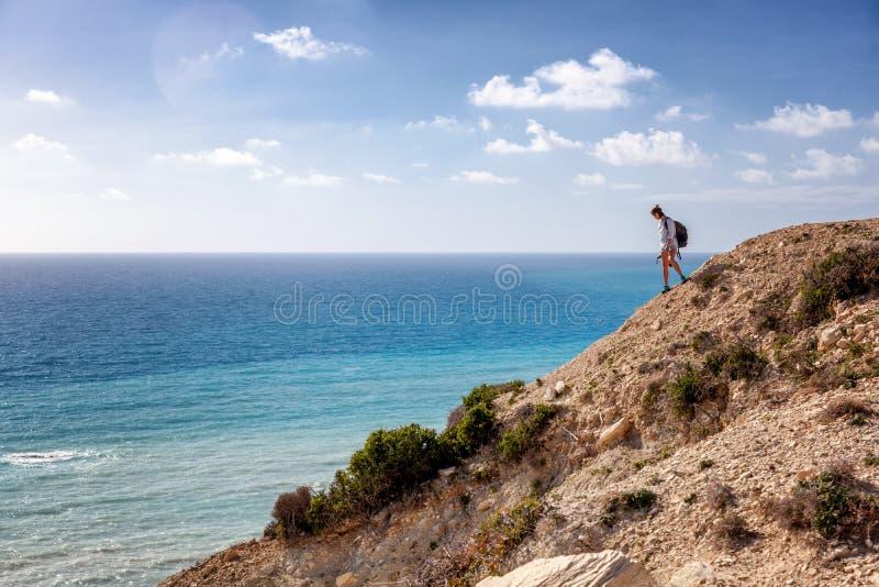 Viajero de la mujer joven en una roca en el fondo del mar, hacia fuera foto de archivo libre de regalías