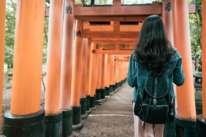 Viajero de la mujer joven que camina en torii imágenes de archivo libres de regalías