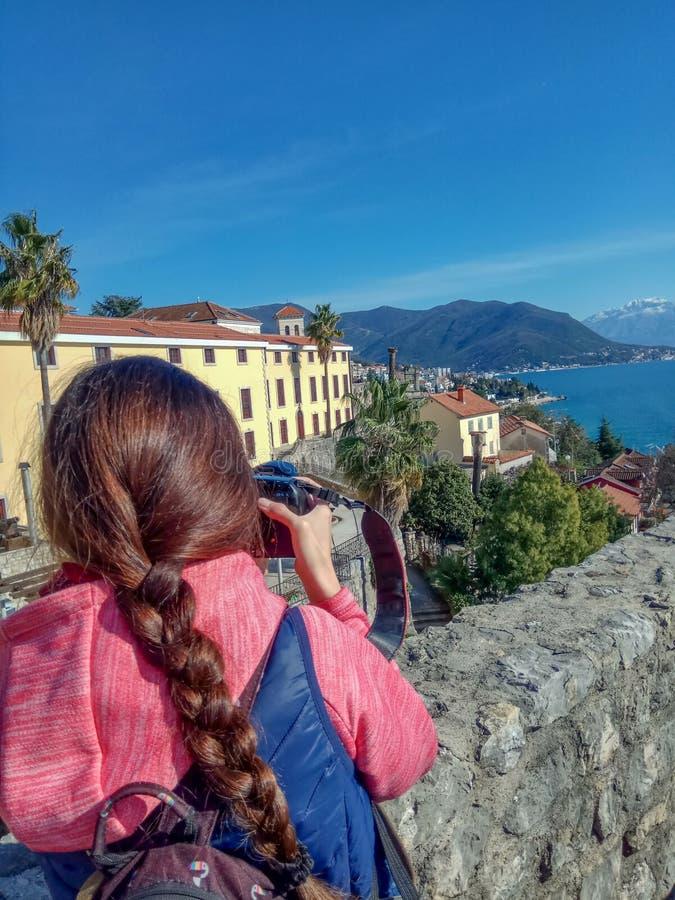 Viajero de la mujer joven que fotografía con la ciudad vieja y las montañas de la cámara profesional de la foto imagen de archivo libre de regalías