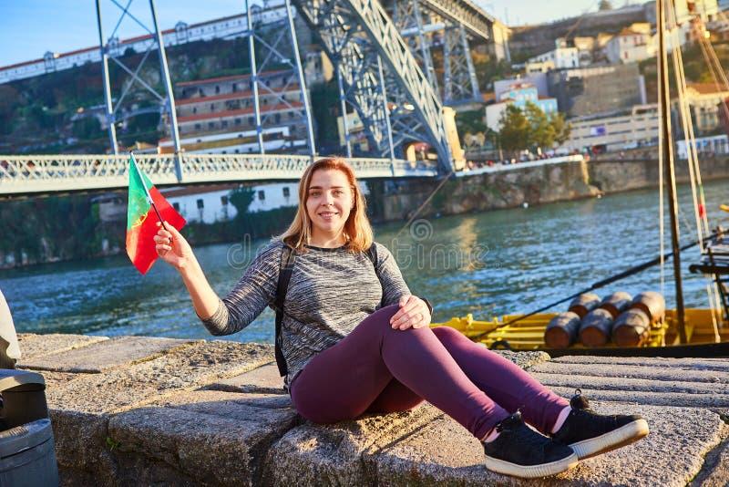 Viajero de la mujer joven que retrocede con la bandera portuguesa, gozando de la opinión hermosa del paisaje urbano sobre el río  foto de archivo