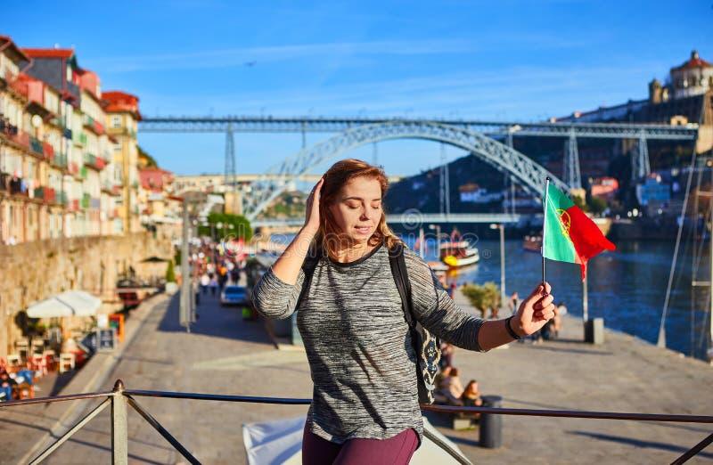 Viajero de la mujer joven que retrocede con la bandera portuguesa, gozando de la opinión hermosa del paisaje urbano sobre el río  fotografía de archivo libre de regalías