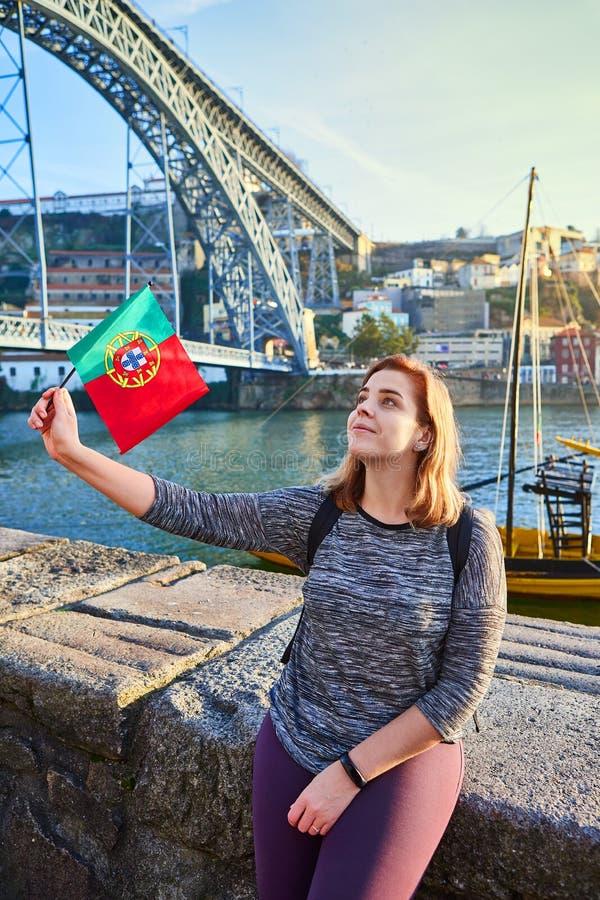 Viajero de la mujer joven que retrocede con la bandera portuguesa, gozando de la opinión hermosa del paisaje urbano sobre el río  fotos de archivo libres de regalías