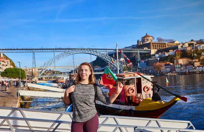 Viajero de la mujer joven que retrocede con la bandera portuguesa, gozando de la opinión hermosa del paisaje urbano sobre el río  imagen de archivo libre de regalías