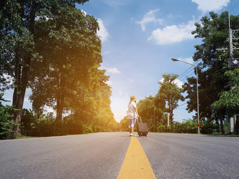 Viajero de la mujer que camina solamente con equipaje a lo largo de la calle imagenes de archivo