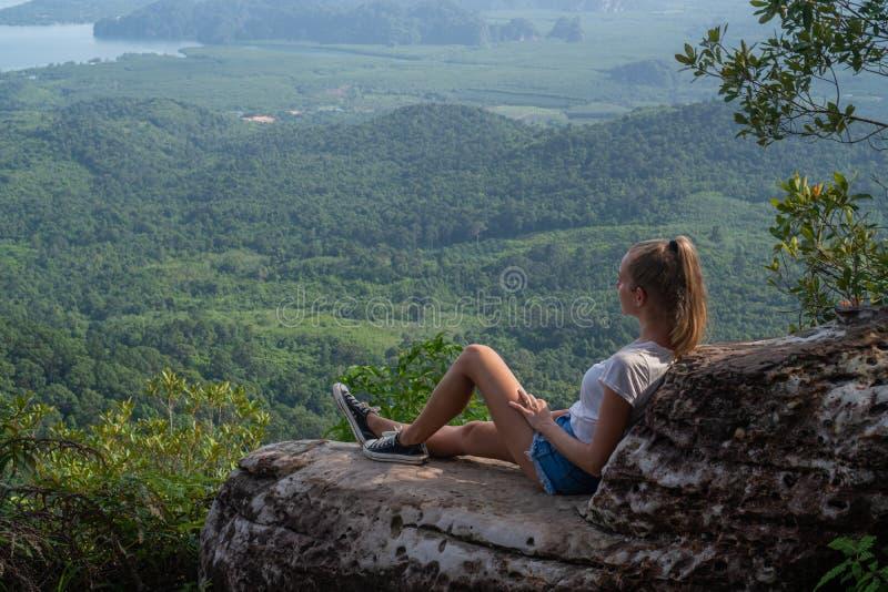 Viajero de la mujer que se sienta en el acantilado fotografía de archivo libre de regalías