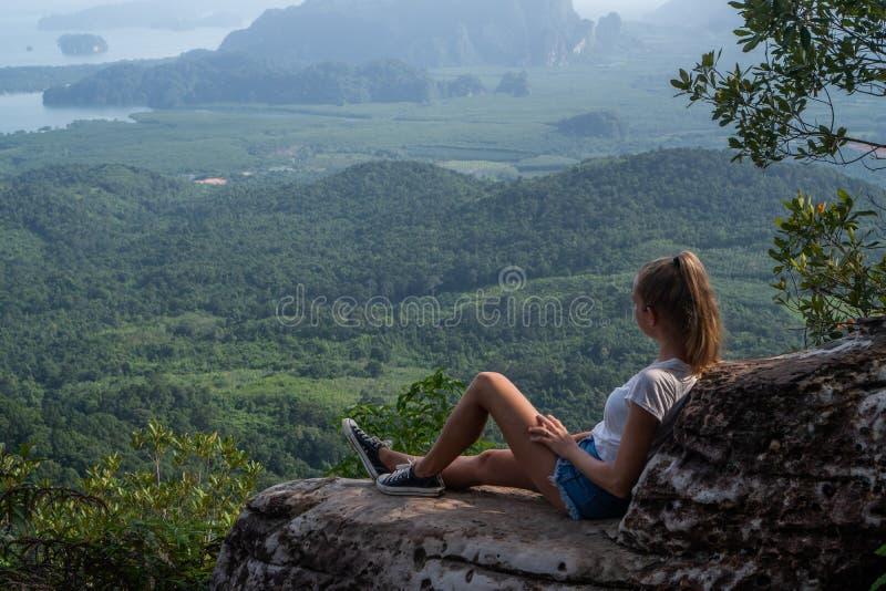 Viajero de la mujer que se sienta en el acantilado imagen de archivo libre de regalías