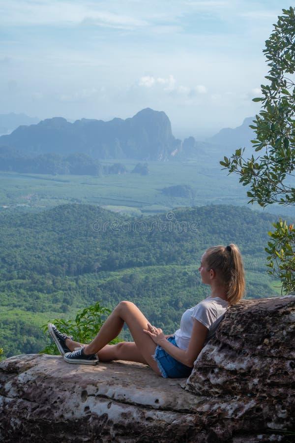 Viajero de la mujer que se sienta en el acantilado fotografía de archivo