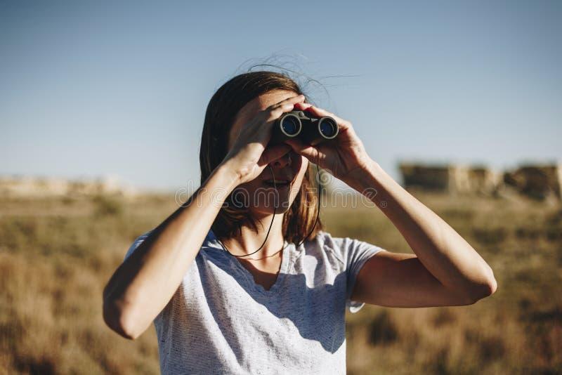 Viajero de la mujer a solas usando los prismáticos imagen de archivo