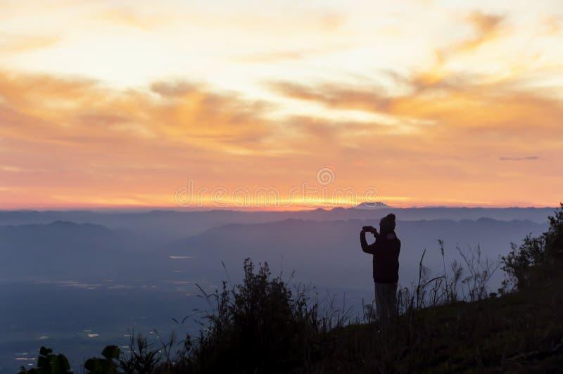Viajero de las mujeres de la silueta que se coloca para ver las montañas de la montaña imagen de archivo libre de regalías