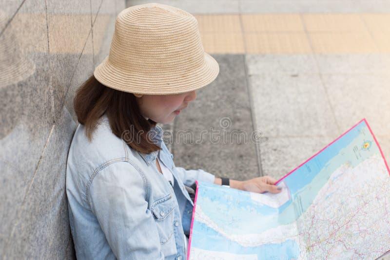 Viajero de las mujeres que mira un mapa para el viaje del plan la ciudad imagenes de archivo