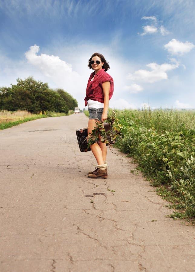 Viajero del auto-stop de la muchacha en el camino imágenes de archivo libres de regalías