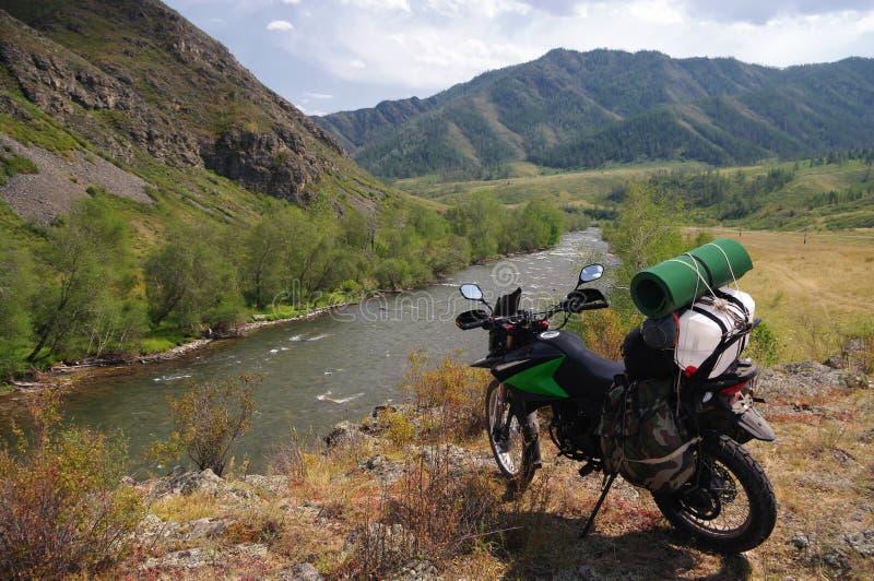 Viajero del enduro de la motocicleta con las maletas que se colocan en una colina superior sobre la corriente del río fotos de archivo