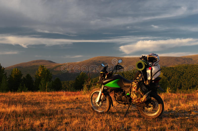 Viajero del enduro de la motocicleta con las maletas que se colocan en una meseta anaranjada ancha del prado de la montaña del am foto de archivo