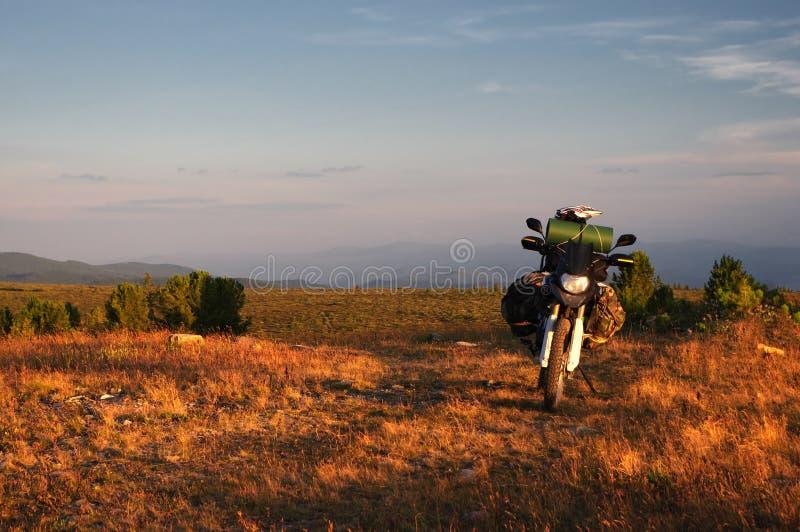 Viajero del enduro de la motocicleta con las maletas que se colocan en una meseta anaranjada ancha del prado de la montaña del am imagen de archivo libre de regalías