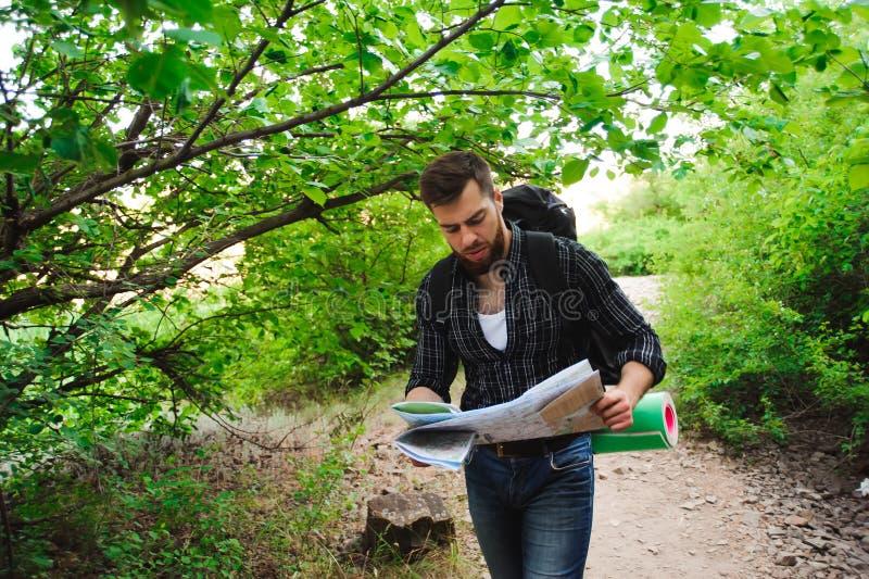 Viajero del hombre joven con la relajación de la mochila del mapa al aire libre en las vacaciones de verano del fondo y la forma  fotografía de archivo
