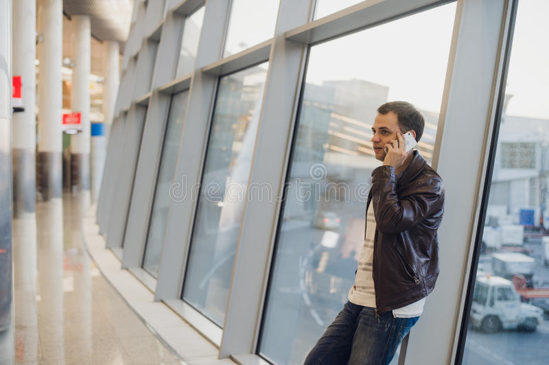 Viajero dentro del terminal de aeropuerto Hombre joven que usa el teléfono móvil y esperando su vuelo fotos de archivo