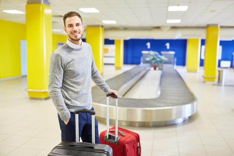 Viajero después de la llegada con las maletas en la correa del equipaje fotos de archivo