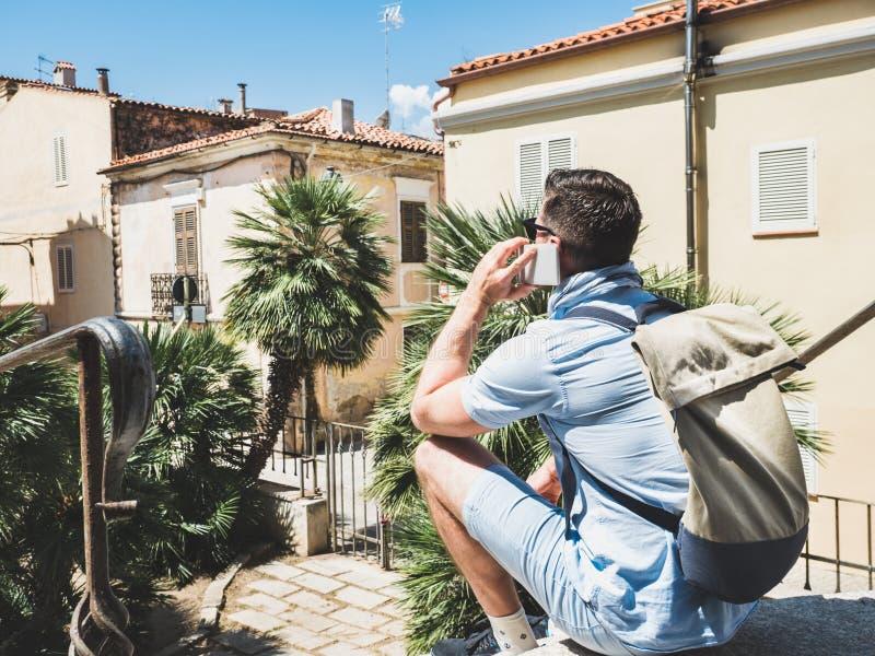 Viajero elegante, atractivo con el smartphone que se sienta en las escaleras fotografía de archivo