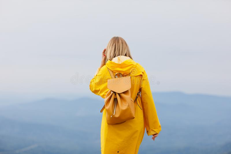 Viajero elegante de la mujer del inconformista con la mochila encima de las montañas, concepto del viaje, espacio para el texto w foto de archivo
