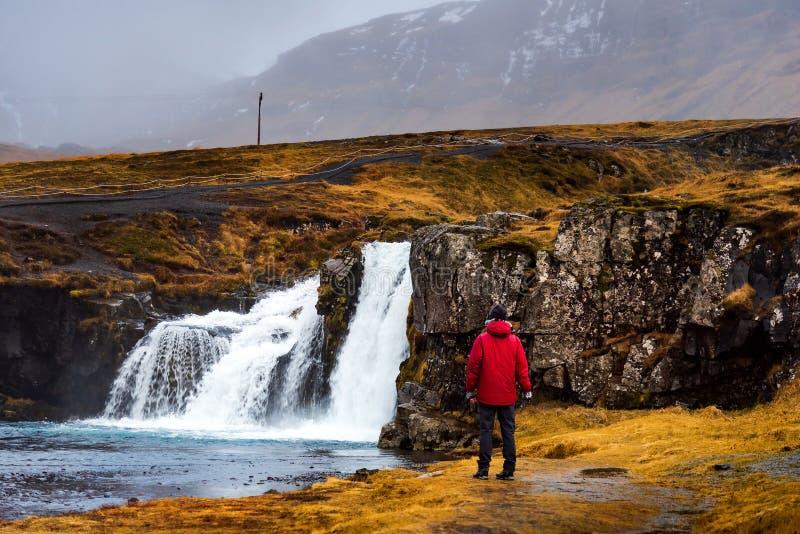 Viajero en la cascada de Kirkjufellsfoss en Islandia fotografía de archivo