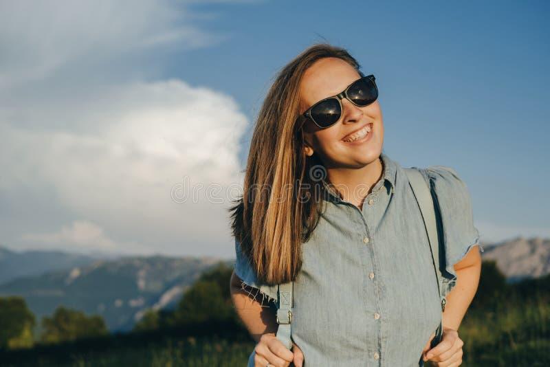 Viajero encantador de la mujer con la mochila y el sunglassesagainst azules fotografía de archivo