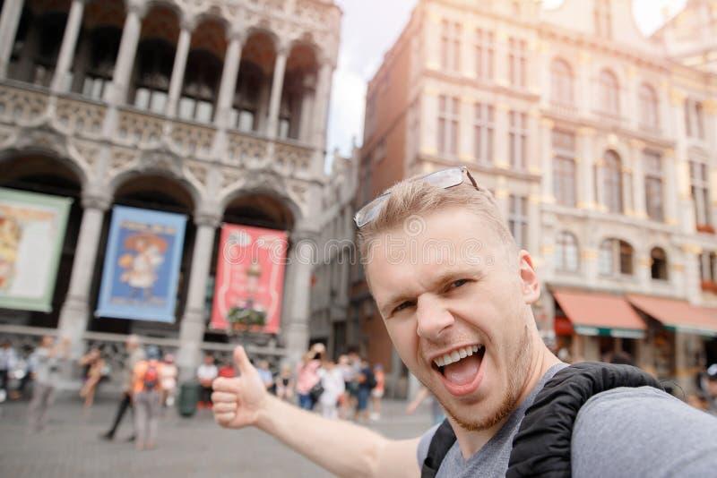 Viajero feliz del hombre con la mochila que toma la foto del selfie en el cuadrado central Bruselas, Bélgica imágenes de archivo libres de regalías