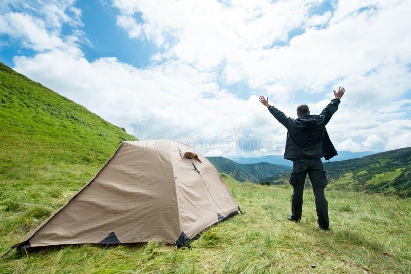 Viajero feliz en las montañas cerca de la tienda imagenes de archivo