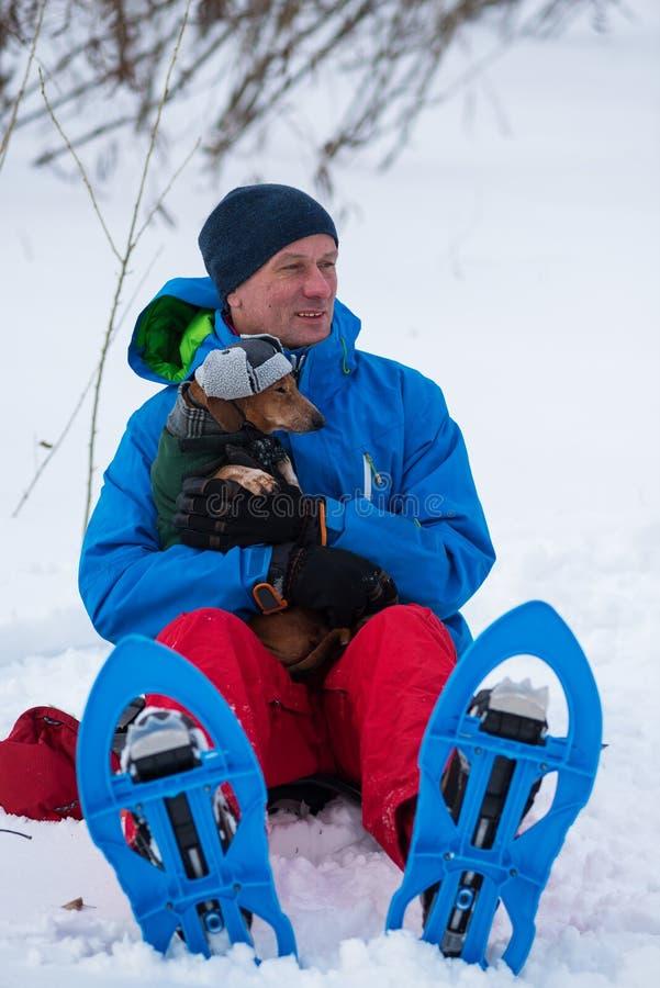 Viajero feliz en las raquetas que abrazan un pequeño perro divertido imágenes de archivo libres de regalías