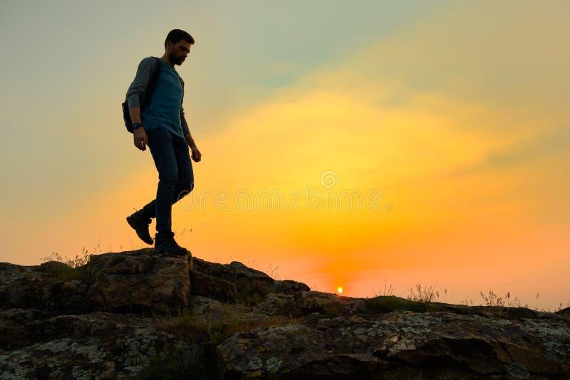 Viajero feliz joven del hombre que camina con la mochila en Rocky Trail en la puesta del sol caliente del verano Concepto del via fotografía de archivo libre de regalías
