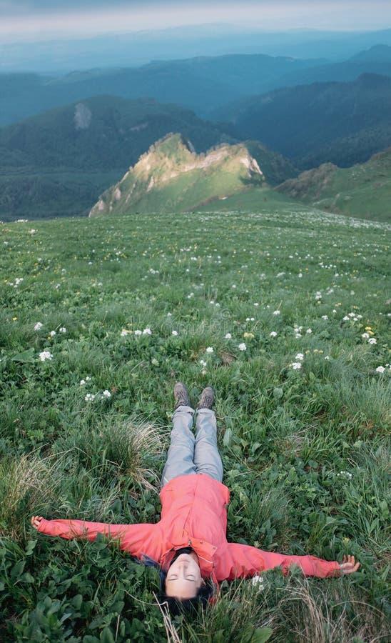 Viajero feliz que miente en prado de la montaña foto de archivo