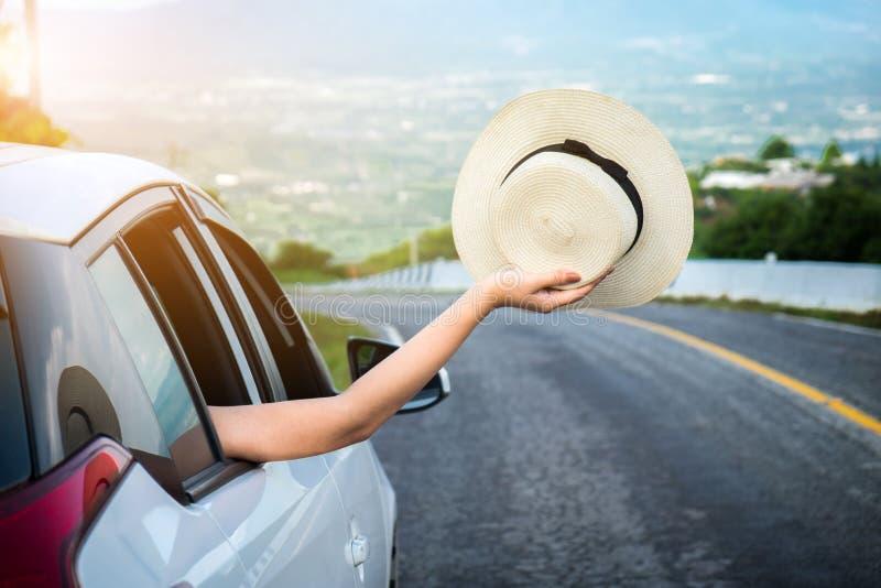 Viajero feliz relajado, gilr asiático hermoso joven que sostiene el sombrero nosotros foto de archivo