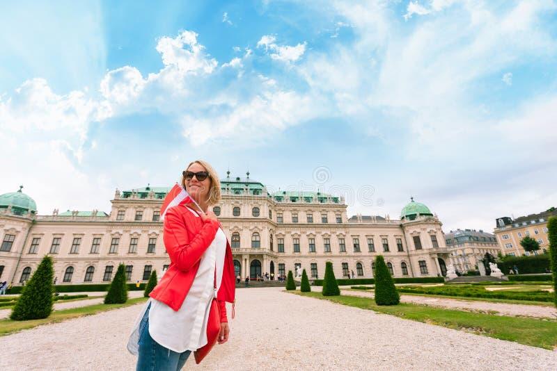 Viajero femenino con la bandera de Austria contra el contexto del palacio superior del belvedere en Viena fotos de archivo libres de regalías