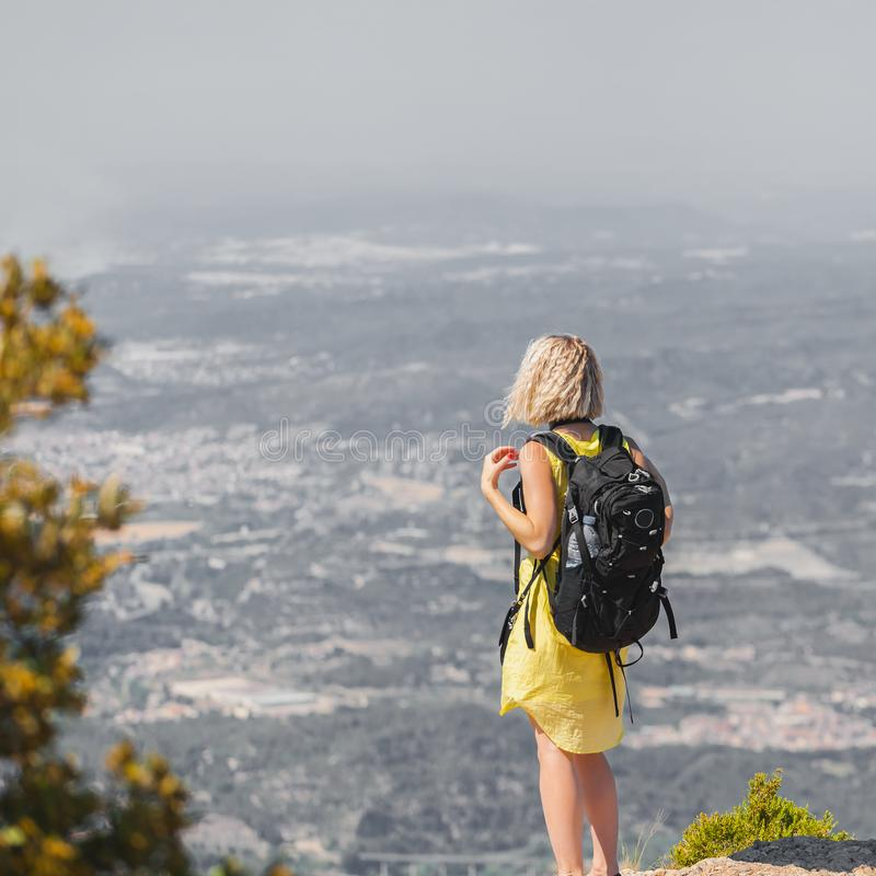 Viajero femenino con una mochila en ella detrás que disfruta de las visiones desde las montañas de Montserrat en España fotos de archivo libres de regalías