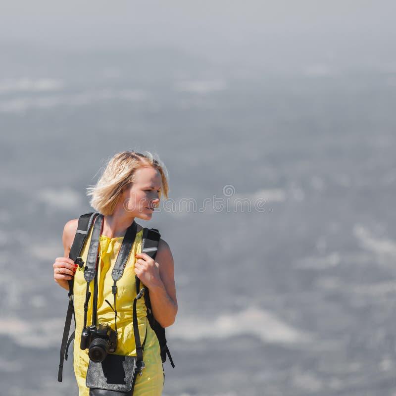 Viajero femenino con una mochila en ella detrás que disfruta de las visiones desde las montañas de Montserrat en España imágenes de archivo libres de regalías