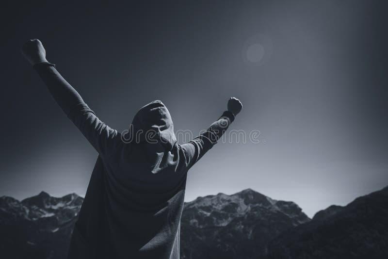 Viajero femenino feliz con las manos aumentadas en el top de la montaña fotos de archivo libres de regalías