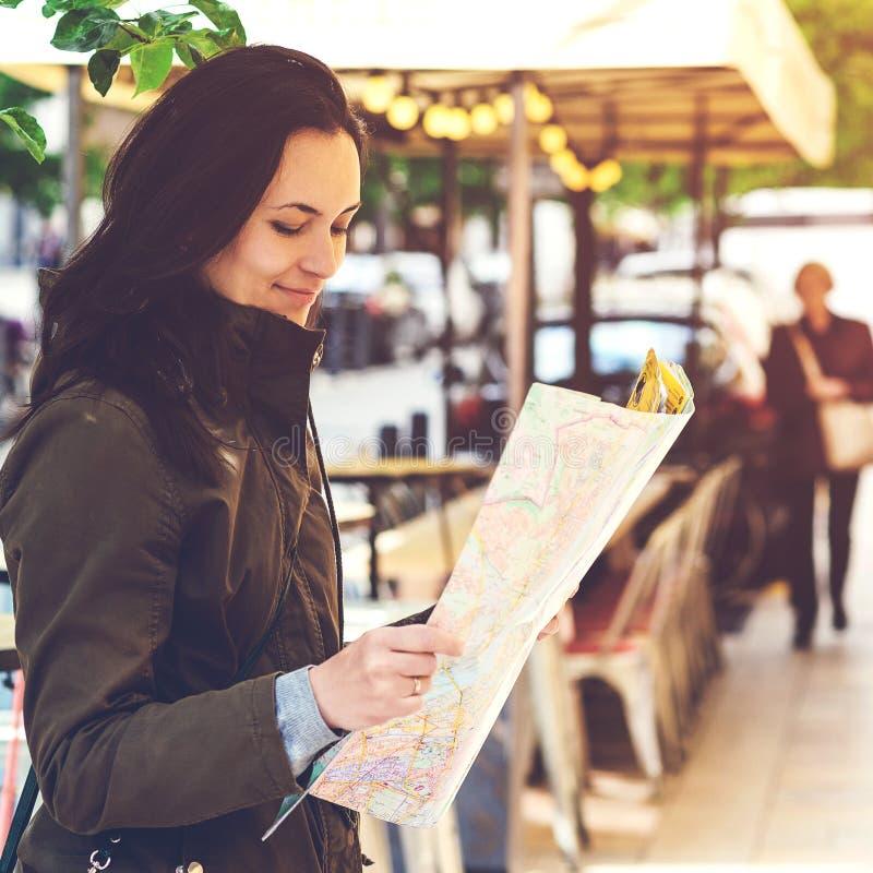 Viajero femenino hermoso joven que se coloca en la calle y que mira el mapa Camino de búsqueda turístico feliz al hotel en mapa e fotografía de archivo libre de regalías