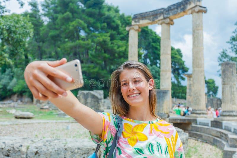Viajero femenino joven que hace el selfie Sitio arqueológico famoso de Olympia Peloponeso, Grecia concepto del recorrido fotografía de archivo