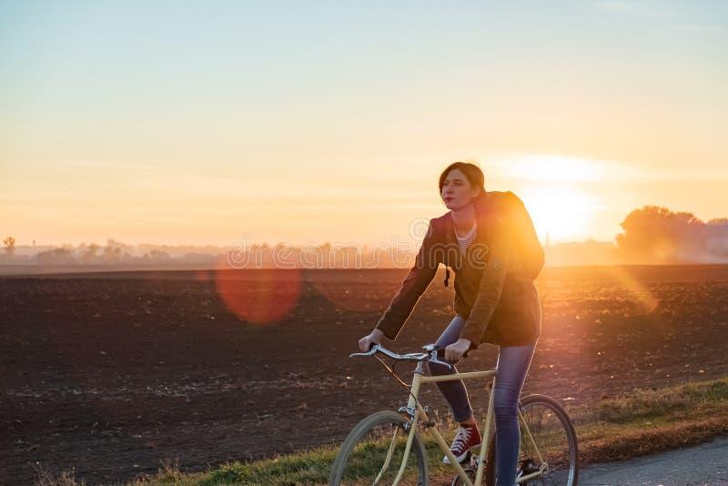 Viajero femenino que monta una bici fuera de ciudad Mujer que completa un ciclo a lo largo de t fotografía de archivo