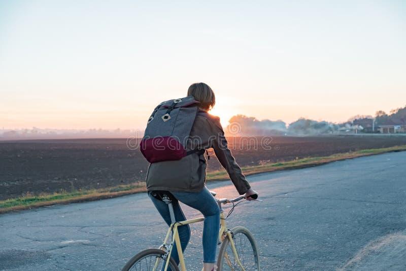 Viajero femenino que monta una bici fuera de ciudad a un área suburbana Yo fotografía de archivo libre de regalías