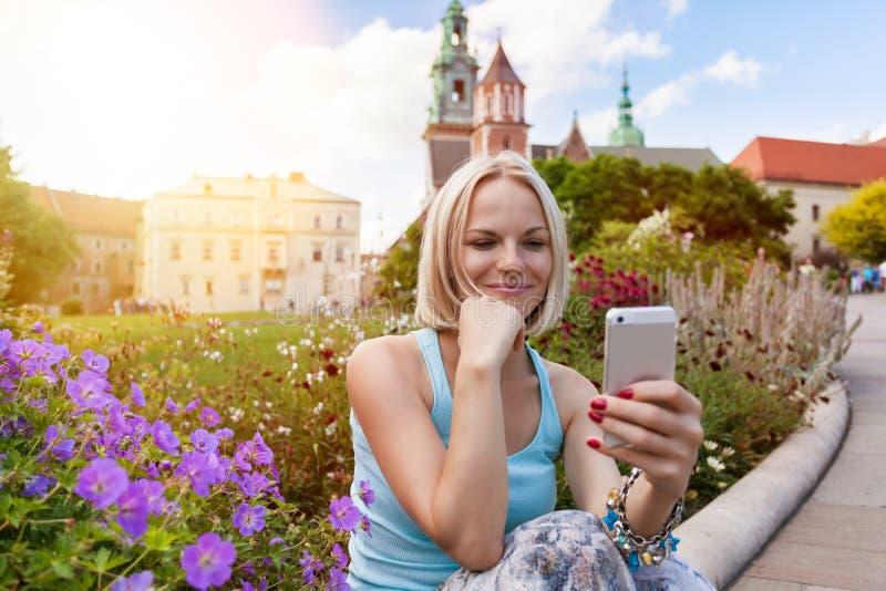 Viajero femenino que se sienta y que mira en un teléfono móvil en el fondo del castillo de Wawel foto de archivo libre de regalías