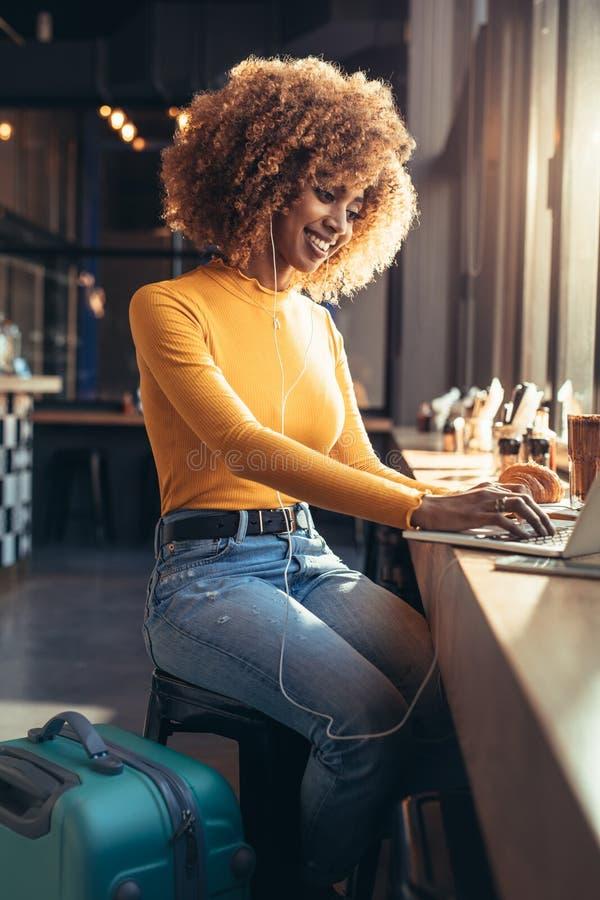 Viajero femenino que trabaja en el ordenador portátil que se sienta en un restaurante foto de archivo libre de regalías