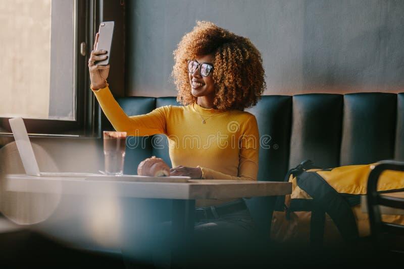 Viajero femenino sonriente que se sienta en una cafetería que toma el selfie foto de archivo