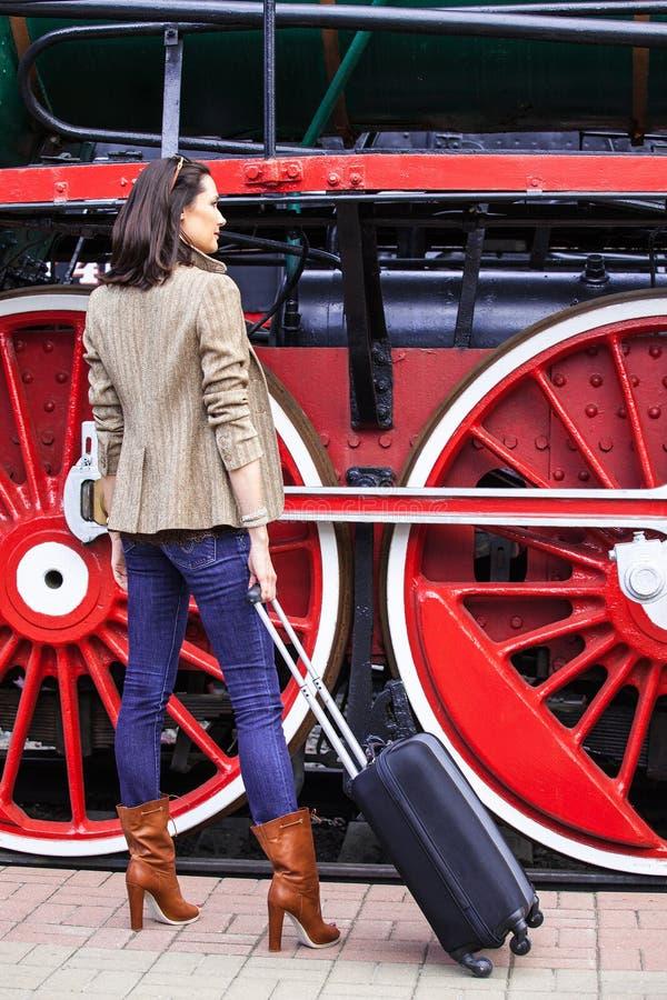 Viajero hermoso de la mujer adulta con una maleta en la plataforma cerca de las ruedas enormes imagenes de archivo
