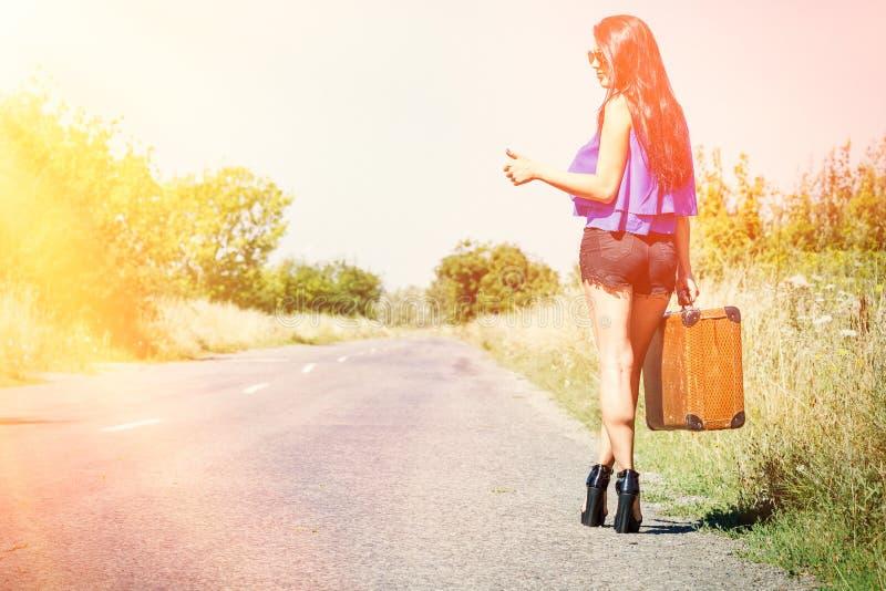 Viajero hermoso feliz de la muchacha con una maleta en el camino, haciendo autostop El concepto de viaje, aventura, vacaciones, l imagen de archivo